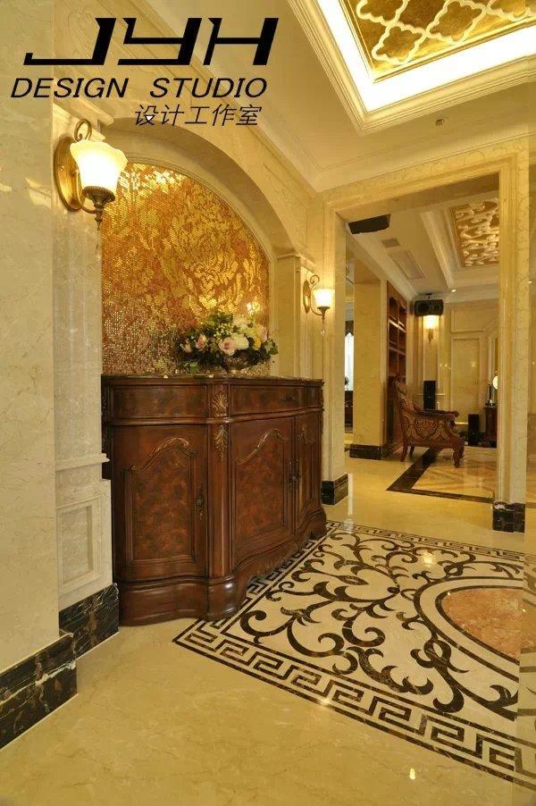 """美式别墅的入室玄关开阔通亮,地面的大理石铺装采用典雅的卷草纹样石材拼花,寓意着吉祥如意,与铺装对应的是顶面精致的金箔元素,奠定了整个室内空间装饰丽堂皇的基调。拱形柱式玄关背景上铺贴的金色繁复花纹的马赛克与 """"维纳城堡""""系列温暖褐色的美式边柜相得益彰。"""